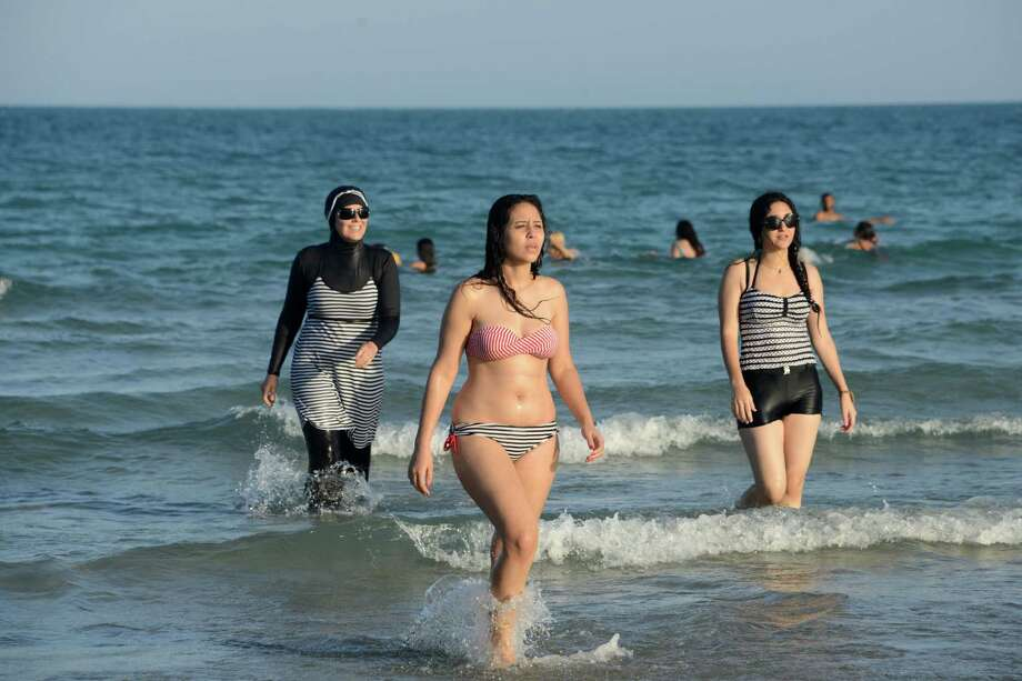 "Tunisian women - the one on the left wearing a ""burkini,"" a full-body swimsuit designed for Muslim women - walk in the water at Ghar El Melh beach near Bizerte, Tunisia. Burkinis are banned on some French beaches. (Fethi Belaid/ AFP/ Getty Images) Photo: FETHI BELAID, Stringer / AFP or licensors"