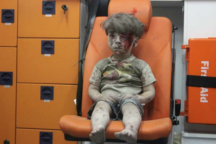 A child sits in an ambulance after being pulled out of a building hit by an airstrike in Aleppo, Syria.