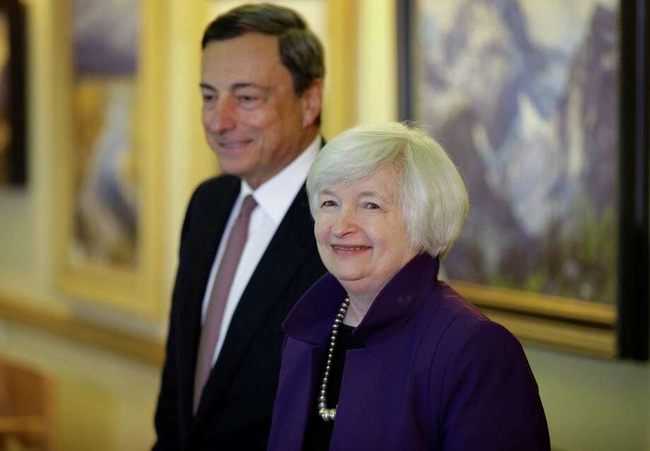 FILE - In this Aug. 22, 2014 file photo, Federal Reserve Chair Janet Yellen, right, and European Central Bank President Mario Draghi walk together during the Jackson Hole Economic Policy Symposium at the Jackson Lake Lodge in Grand Teton National Park near Jackson, Wyo. Record low interest rates were meant to be a temporary response to the global financial crisis. But eight years later, rates are still near zero in much of the developed world - and some experts are warning of long-term side effects. The Federal Reserve lowered its short-term benchmark - which determines the cost of overnight lending between banks - to between zero and 0.25 percent in December 2008. The European Central Bank reached zero in March and the Bank of Japan in late 2010. Just last week, the Bank of England cut its benchmark rate to 0.25 percent and indicated it could bring it closer to zero. (AP Photo/John Locher, file) Photo: John Locher, STF / Associated Press / Copyright 2016 The Associated Press. All rights reserved. This material may not be published, broadcast, rewritten or redistribu