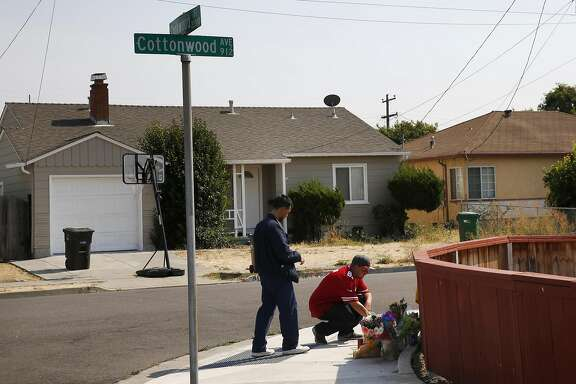 Two men who only wanted to be identified as friends of Jason Villigas pay their respects at a memorial at the site where Villigas, 42, died on Aug. 14 as he tried to stumble home after he was stabbed repeatedly nearby August 18, 2016 in Hayward, Calif.