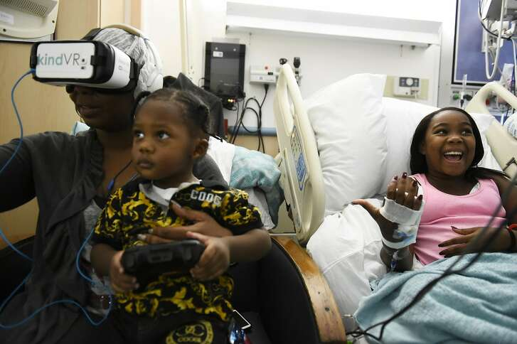 """Briana Nathaniel,14, laughs as her mother Latonji Williams experiences her first VR session on August 9, 2016 at UCSF Benioff Children's Hospital in Oakland, California. """"It's like your swimming with the fish, dolphins and whales"""" said Nathaniel."""