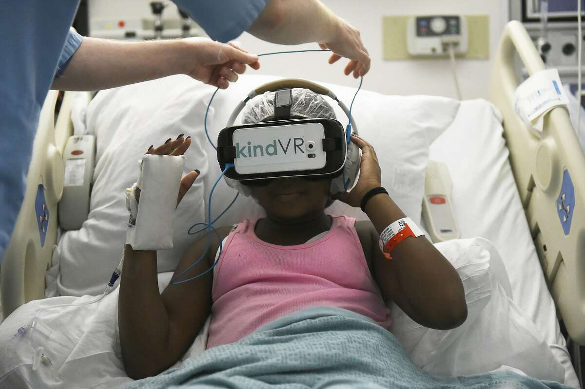 Simon Robertson adjust headphones on Briana Nathaniel,14, during her 15 minute VR session on August 9, 2016 at UCSF Benioff Children's Hospital in Oakland, California. Nathaniel suffers pain related to sickle cell.