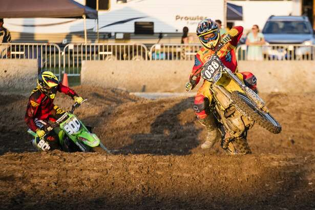 Randy Woodring, left, and Shane Larsen, right, come around a turn during the 250A race at the Super Cross race event at the Midland County Fair on Friday.
