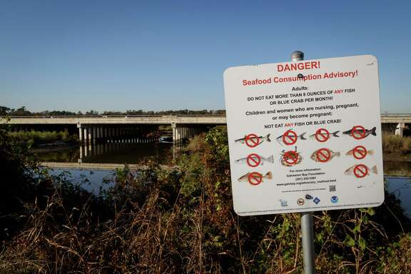 A sign near the San Jacinto River warns against eating contaminated seafood caught from the water due to the toxic sludge submerged there.