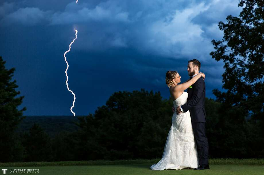 """Even in a thunderstorm, there is opportunity. That certainly was the case for wedding photographer Justin Tibbitts. He was shooting Waterford couple Katherine and Greg Cresci's wedding on Aug. 13 at the Albany Country Club when the massive storm started rolling through. The lensman said when he saw what was coming he ran in and grabbed bride and groom, who were just sitting down to dinner, and convinced them to go outside. """"My assistant illuminated them from the side as I sat on the ground and balanced my camera on my knees for a steady shot,"""" Tibbitts said. """"With my face glued to the viewfinder waiting for a flash in the sky off into the distance, I could just sense that I was going to capture one of the rarest shots known in wedding photography. My heart was racing, and after a few minutes of waiting, we finally got that flash in the sky. As soon as I saw the flash in my viewfinder, I clicked my shutter, and then there it was, a full lightning bolt was captured in the image with Katherine and Greg. What a moment that was for all of us!"""" Photo: Justin Tibbitts / Justin Tibbitts Photography"""