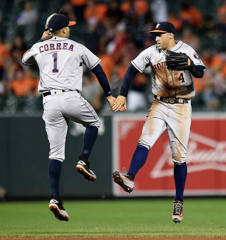 Houston Astros' Carlos Correa, left, and George Springer celebrate the team's 15-8 win over the Baltimore Orioles in a baseball game, Friday, Aug. 19, 2016, in Baltimore. (AP Photo/Gail Burton) Photo: Gail Burton, Associated Press / FR4095 AP