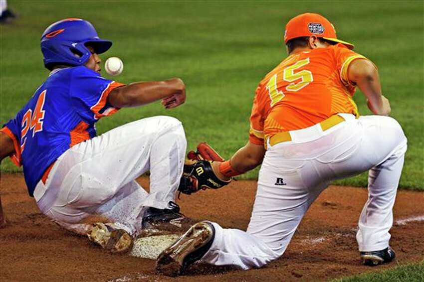 Bowling Green, Ky.'s Devin Obee, left, slides safely into third as the throw from San Antonio, Tex., catcher Blake Compton gets away from third baseman Rilan Quinones (15) during the second inning of a baseball game in United States pool play at the Little League World Series tournament in South Williamsport, Pa., Friday, Aug. 19, 2016. Obee scored on the throwing error. (AP Photo/Gene J. Puskar)