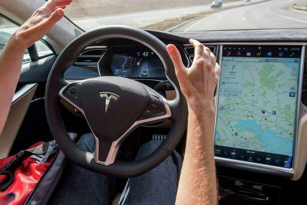 A reporter test drives a Tesla Model S car equipped with Autopilot. New rules for self-driving cars are being written by regulators.
