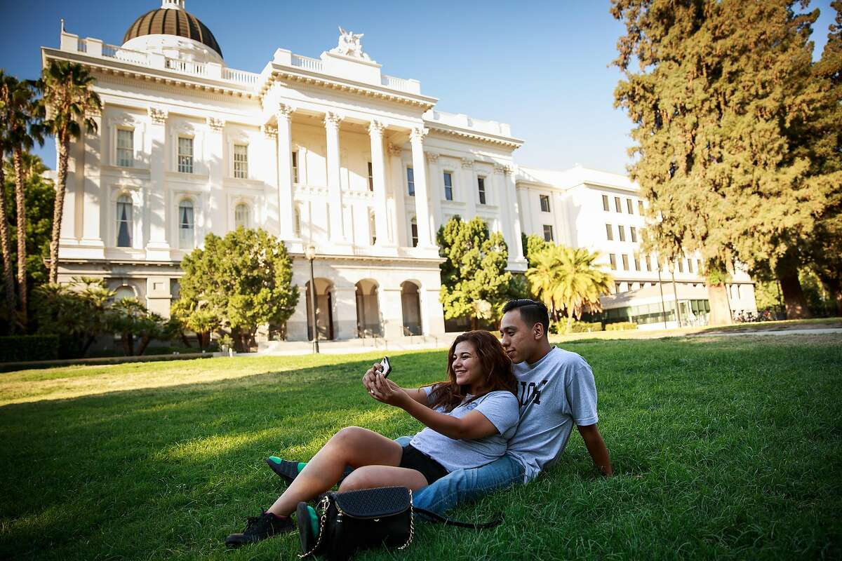 Corina Sandoval and Wallace Virgen takes selfies on the lawn of The State Capitol in Sacramento, California, August 15, 2015.