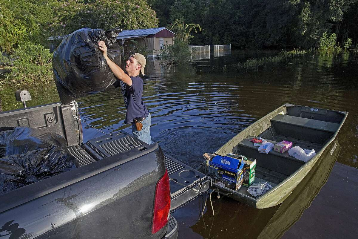 Daniel Stover, 17, loads personal belongings from a friend's home flooded home in Sorrento, La., Saturday, Aug. 20, 2016. Louisiana continues to dig itself out from devastating floods, with search parties going door to door looking for survivors or bodies trapped by flooding. (AP Photo/Max Becherer)