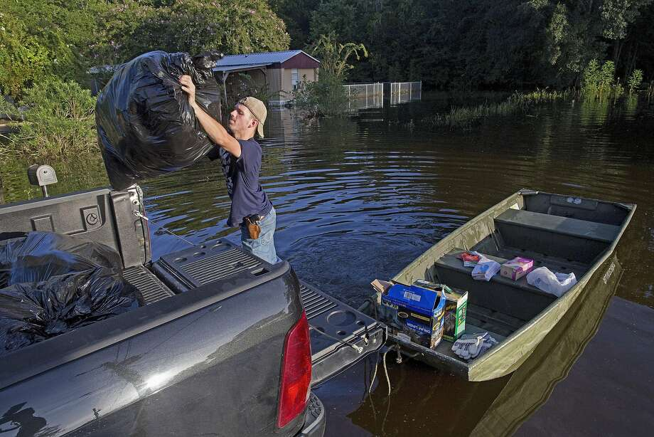 Daniel Stover loads belongings from a friend's flooded home in Sorrento, La. At least 13 people have died in the flooding that swept through southern Louisiana after torrential rains. Photo: Max Becherer, Associated Press