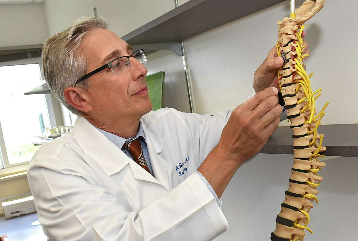 Dr. Darryl DiRisio neurosurgeon, department of neurosurgery, places a reveal device on a ReVivo spine model at the Biomedical Acceleration Commercialization Center at Albany Medical Center on Thursday, Aug. 18, 2016 in Albany, N.Y. (Lori Van Buren / Times Union)