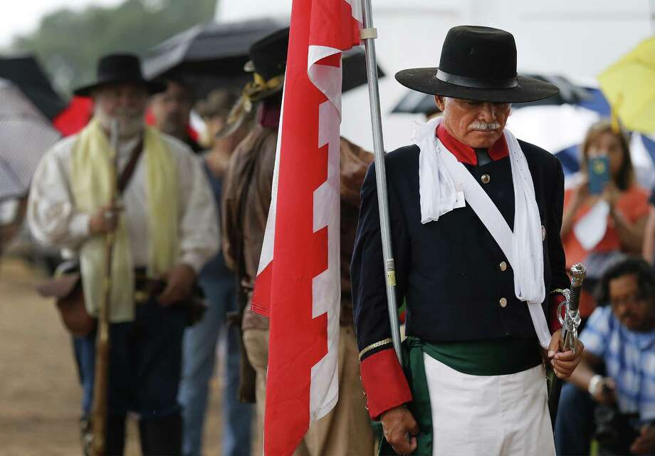 Dan Arellano (foreground), president of Battle of Medina Society, lowers his head, carrying a Burgundian cross flag and dressed as an officer of the Spanish Royal Army, during a prayer, as a small gathering of historians, descendants and the public commemorate the fallen of the Battle of Medina in 2016. Members of several living history associations wore period clothing while firing musket volleys to mark the occasion. The Battle of Medina, which occurred on August 18, 1813, is considered by historians the bloodiest battle ever fought on Texas soil. Photo: Kin Man Hui /San Antonio Express-News / ©2016 San Antonio Express-News