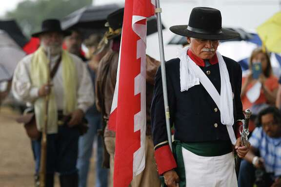 Dan Arellano (foreground), president of Battle of Medina Society, lowers his head, carrying a Burgundian cross flag and dressed as an officer of the Spanish Royal Army, during a prayer, as a small gathering of historians, descendants and the public commemorate the fallen of the Battle of Medina in 2016. Members of several living history associations wore period clothing while firing musket volleys to mark the occasion. The Battle of Medina, which occurred on August 18, 1813, is considered by historians the bloodiest battle ever fought on Texas soil.
