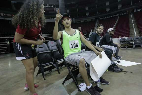 Dean Sivorakoune goes over instructions with an assistant for his 90-second routine during the open auditions for Clutch, the Houston Rockets mascot, at the Toyota Center on Saturday, Aug. 20, 2016, in Houston.