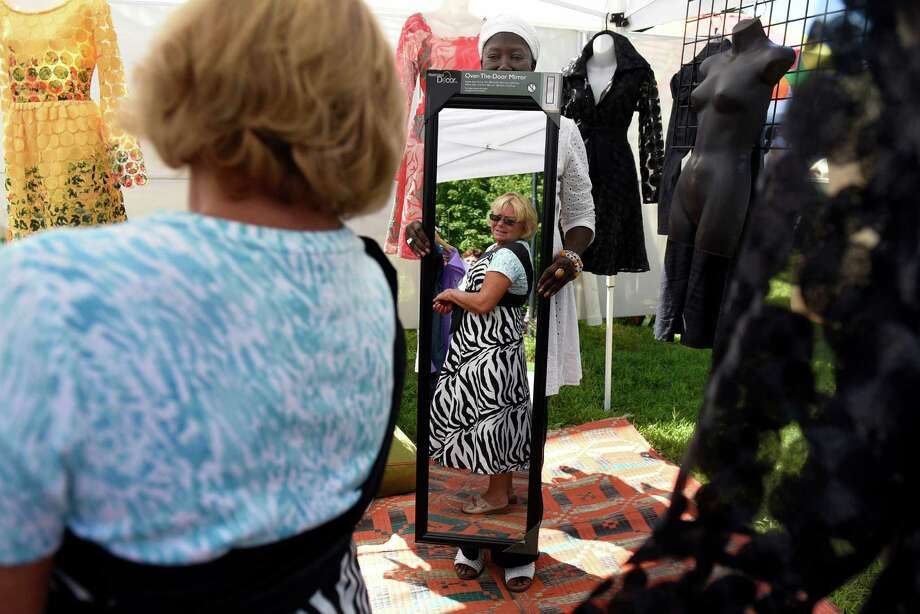Linda Cocozzo of Saratoga Springs, checks out her reflection when she tries out a wrap dress during the Saratoga Arts Celebration on Saturday, Aug. 20, 2016, at the National Museum of Dance in Saratoga Springs, N.Y. Aita Carmichael of Harlem holds the mirror in her La Linguere Fashion booth. The juried art show continues Sunday from 10 a.m. to 5 p.m. (Cindy Schultz / Times Union) Photo: Cindy Schultz / Albany Times Union