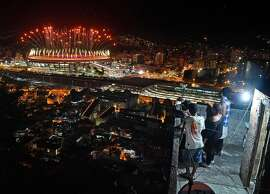 TOPSHOT - People watch fireworks exploding over the Maracana stadium, from a terrace in the favela Mangueira, during the opening ceremony of the Rio 2016 Olympic Games in Rio de Janeiro on August 5, 2016. / AFP PHOTO / Andrej ISAKOVICANDREJ ISAKOVIC/AFP/Getty Images