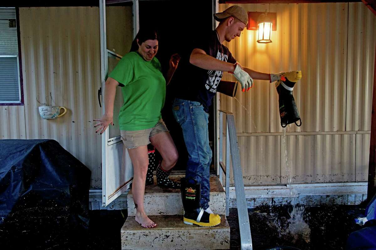 Shelley DeCarlo, 40, left, and Daniel Stover, 17, empty their boots of water as they enter the home of Laura Albritton to help her save some personal belongings from floodwater in Sorrento, La., on Saturday. ,
