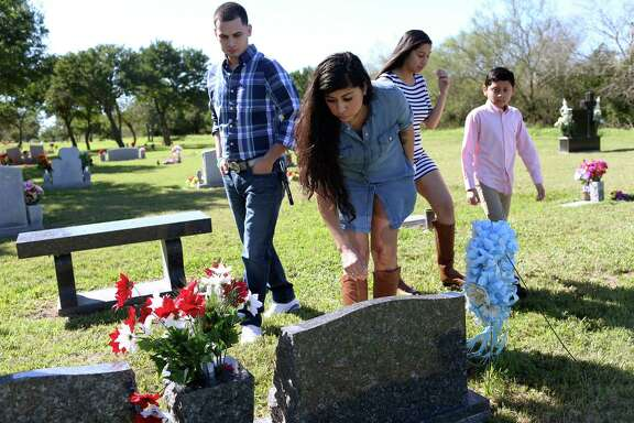 Denise Cantu, 36, center, and her family visit the gravesite of her children, Annissa Marie Salazar and Johnathon Dominic Cortez at the Monte Meta Cemetery near San Benito in January. The two children were killed in an auto accident in 2010 near Pleasanton after their vehicle lost its right year a tire in their vehicle blew out. She invested proceeds from an insurance settlement from that accident with San Antonio frac sand company FWLL LLC, doing business as FourWinds Logistics. FourWinds lost her investment and she had sued the company before it filed for bankruptcy. Her son was 5 years old and her daughter was 14 years old at the time of their death. With Cantu are her fiancée, Andrew Reyna (left), 27, and her daughter, Jasmin Conde, 15, and son, Ryan Yanez, 11.