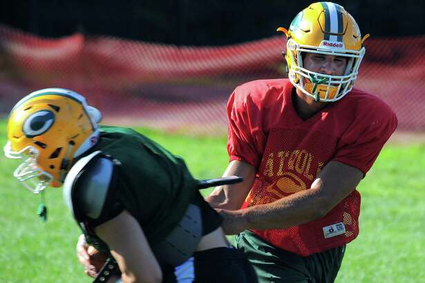 Trinity Catholic quarterback Nick Granata hands off the ball during practice at the high school in Stamford on Thursday.