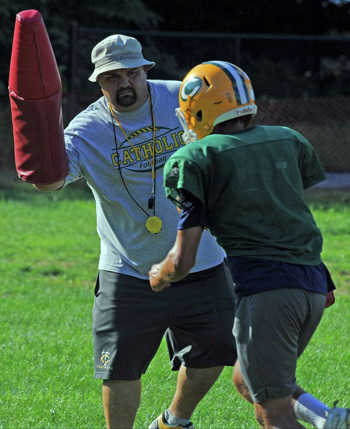 Trinity Catholic Coach Donny Panapada joins in on a drill during football practice on Thursday.