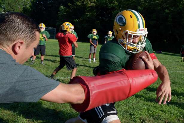 A coach attempts to jar the ball from Trinity Catholic running back John Michael Bivona during practice on Thursday.