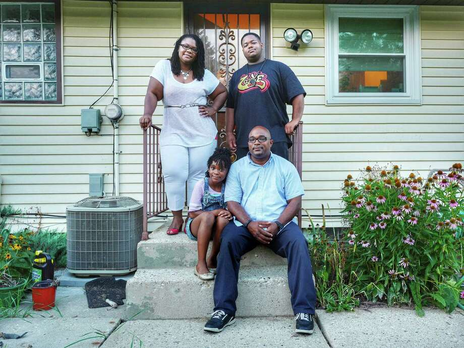X'antony Brookens Sr., seated, and his wife, Latisha Spence-Brookens, with their children X'antony Jr. and Zaria at their new home in the far north side of Milwaukee, Aug. 18, 2016. The Brookens family recently returned to Milwaukee from Whitefish Bay, a distant north suburb so white it is known locally as Whitefolks Bay; for them, the sense of community has trumped the fear of crime. (Ruddy Roye/The New York Times) ORG XMIT: XNYT19 Photo: RUDDY ROYE / NYTNS