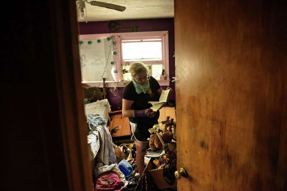 Cheyenne Hughes looks at a bible while salvaging items in her family's home after flooding August 17, 2016 in Denham Springs, Louisiana. The death toll from historic flooding in Louisiana climbed to 11 on August 16 as the expanding flood zone prompted authorities to declare disasters in 20 parishes of the southeastern US state. / AFP PHOTO / Brendan SmialowskiBRENDAN SMIALOWSKI/AFP/Getty Images ORG XMIT: Torrentia Photo: BRENDAN SMIALOWSKI / AFP or licensors