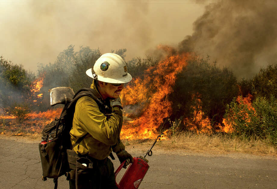 A U.S. Forest Service firefighter moves away from a quickly moving section of the Rim Fire in the Stanislaus National Forest Tuesday, Aug. 20, 2013. (AP Photo/The Modesto Bee, Andy Alfaro) LOCAL TV OUT (KXTV10, KCRA3, KOVR13, FOX40, KMAX31, KQCA58, CENTRAL VALLEY TV); LOCAL PRINT OUT (TURLOCK JOURNAL, CERES COURIER, OAKDALE LEADER, MODESTO VIEW, PATTERSON IRRIGATOR, MANTECA BULLETIN, RIPON, RECROD, SONORA UNION DEMOCRAT, AMADOR LEDGER DISPATCH, ESCALON TIMES, CALAVERAS ENTERPRISE, RIVERBANKS NEWS) LOCAL INTERNET OUT (TURLOCK CITY NEWS.COM, MOTHER LODE.COM)  ORG XMIT: CAMOD101 Photo: Andy Alfaro / Modesto Bee