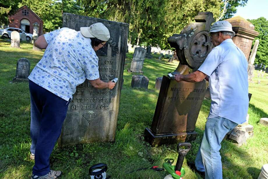 Mary Upton, left, of Schenectady and Bill Preston of Ballston Spa clean headstones at the Ballston Spa Village Cemetery on Saturday Aug. 20, 2016 in Ballston Spa, N.Y. (Michael P. Farrell/Times Union) Photo: Michael P. Farrell / 20037730A