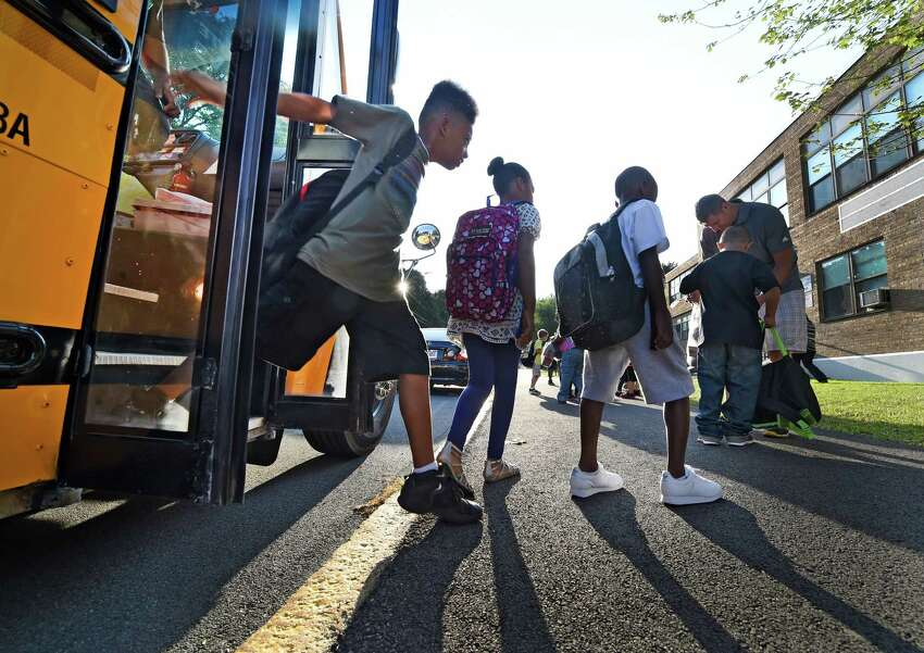 Students disembark a school bus Wednesday morning Sept. 9, 2015, as they arrive for opening day at Public School 16 in Troy, N.Y. (Skip Dickstein/Times Union)