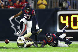 Houston Texans strong safety Quintin Demps (27) leaps up over Texans cornerback A.J. Bouye (21) and New Orleans Saints wide receiver Brandon Coleman (16) during the second quarter of an NFL game at NRG Stadium, Saturday, Aug. 20, {year}, in Houston.