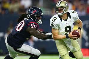 New Orleans Saints quarterback Drew Brees (9) tries to scramble away from Houston Texans outside linebacker Jadeveon Clowney (90) just before getting sacked during the second quarter of an NFL game at NRG Stadium, Saturday, Aug. 20, {year}, in Houston.