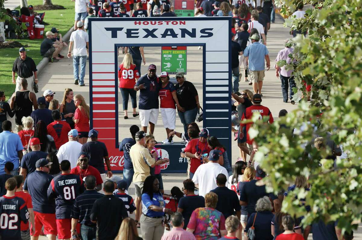 Fans take photos in front of NRG Stadium before the Houston Texans preseason game against the New Orleans Saints Saturday, Aug. 20, 2016, in Houston .