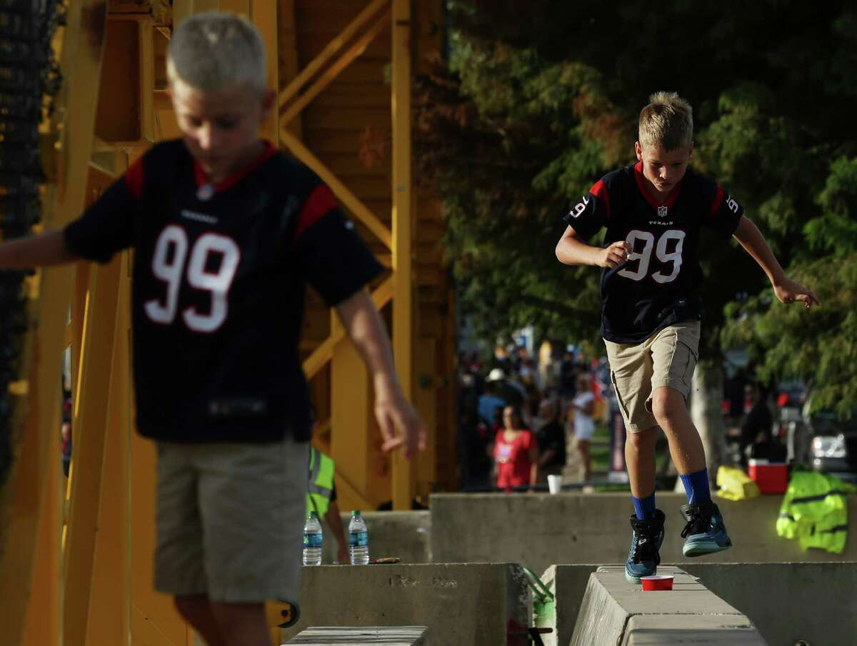 Two kids play at the parking lot before the Houston Texans preseason game against the New Orleans Saints Saturday, Aug. 20, 2016, in Houston .