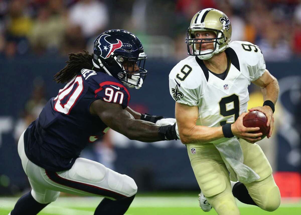 Saints quarterback Drew Brees (9) tries to scramble away from Texans outside linebacker Jadeveon Clowney (90) just before Clowney brought down Brees.