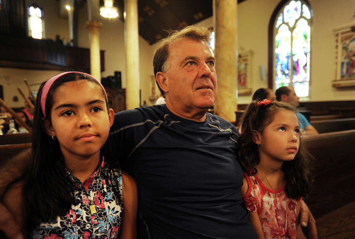 Marcelo Meirelles, of Bridgeport, attends morning Mass in Brazilian Portugues with his daughters Joyce, 11, left, and Julie Meirelles, 7, at St. Charles Borromeo Catholic Church in Bridgeport last Sunday.