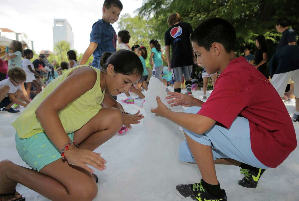 Houston siblings Aileen, 10, and Jonathan Guzman, 12, build a snowman during Snow Day at the Zoo on Saturday, Aug. 20, 2016, in Houston.