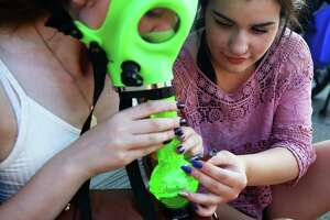 D.J., right, helps Savannah smoke from a gas mask bong on day two of Hempfest, the annual cannabis freedom festival at Myrtle Edwards Park on the Seattle waterfront. The three day festival is an annual Seattle tradition that started in 1991. This year marks the 25th annual event. Photographed on Saturday, August 20, 2016. (