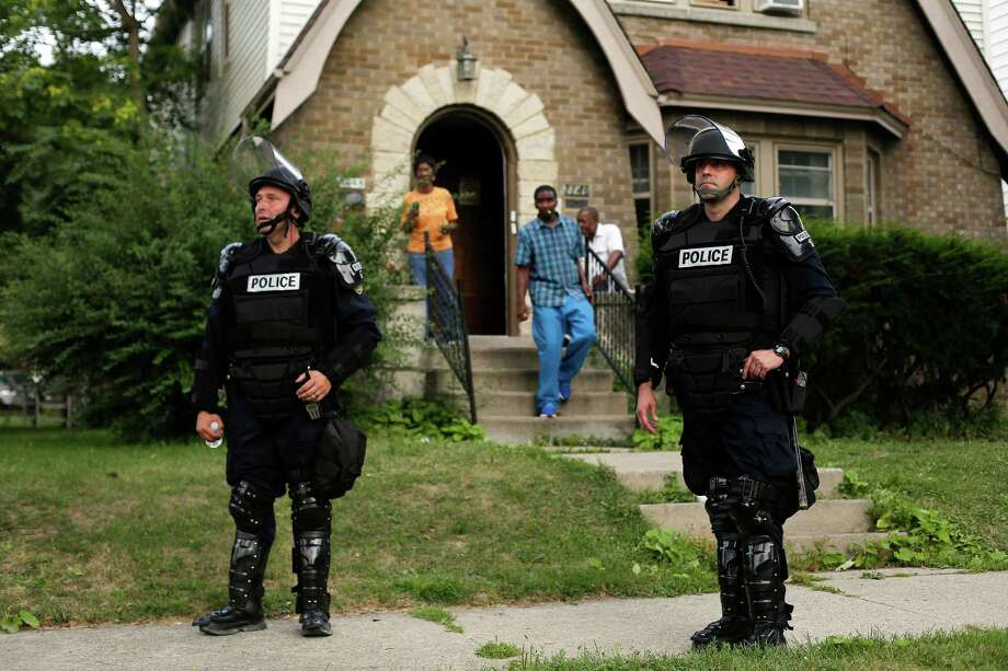 FILE -- Police officers in riot gear near Sherman Park where a curfew was in effect  after unrest caused by the fatal police shooting of a black man, in Milwaukee, Aug. 15, 2016. African-Americans in Milwaukee worry that the elimination of a residency requirement for police officers will worsen a long-strained relationship with the community. (Joshua Lott/The New York Times) Photo: JOSHUA LOTT / NYT / NYTNS