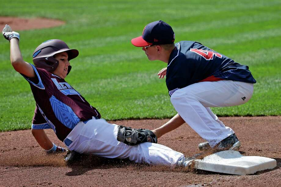 Warwick, Rhode Island's Domenic Brazeau, left, is tagged out by Endwell, N.Y.'s third baseman Brody Raleigh (4) during the first inning of United States pool play at the Little League World Series tournament in South Williamsport, Pa., Thursday, Aug. 18, 2016. (AP Photo/Gene J. Puskar) ORG XMIT: PAGP132 Photo: Gene J. Puskar / Copyright 2016 The Associated Press. All rights reserved. This m
