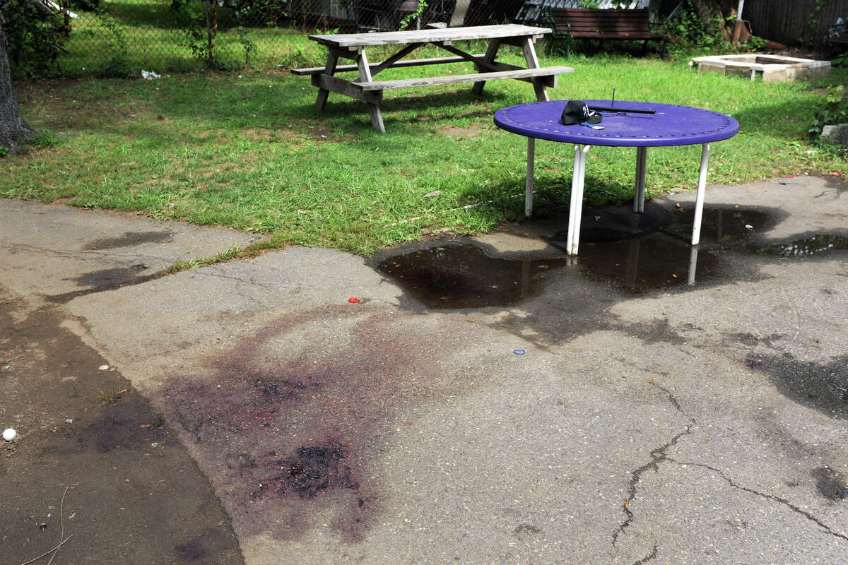 Blood stains on the pavement behind 19-21 Plymouth St., in Bridgeport, Conn. Aug. 21, 2016. Police report that 13 people were hit by gunfire while attending a backyard party at this location early Sunday morning.