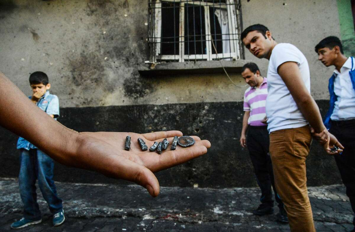 TOPSHOT - A person shows pieces of projectile near the explosion scene following a late night attack on a wedding party that left at least 30 dead in Gaziantep in southeastern Turkey near the Syrian border on August 21, 2016. Turkish President Recep Tayyip Erdogan on Sunday said the Islamic State (IS) group was the