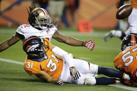 San Francisco 49ers running back DuJuan Harris, back left, watches his fumble as he goes down next to Denver Broncos free safety Justin Simmons (31) in the end zone during the second half of a preseason NFL football game, Saturday, Aug. 20, 2016, in Denver. The Broncos recovered the ball for a touchback. (AP Photo/Jack Dempsey)