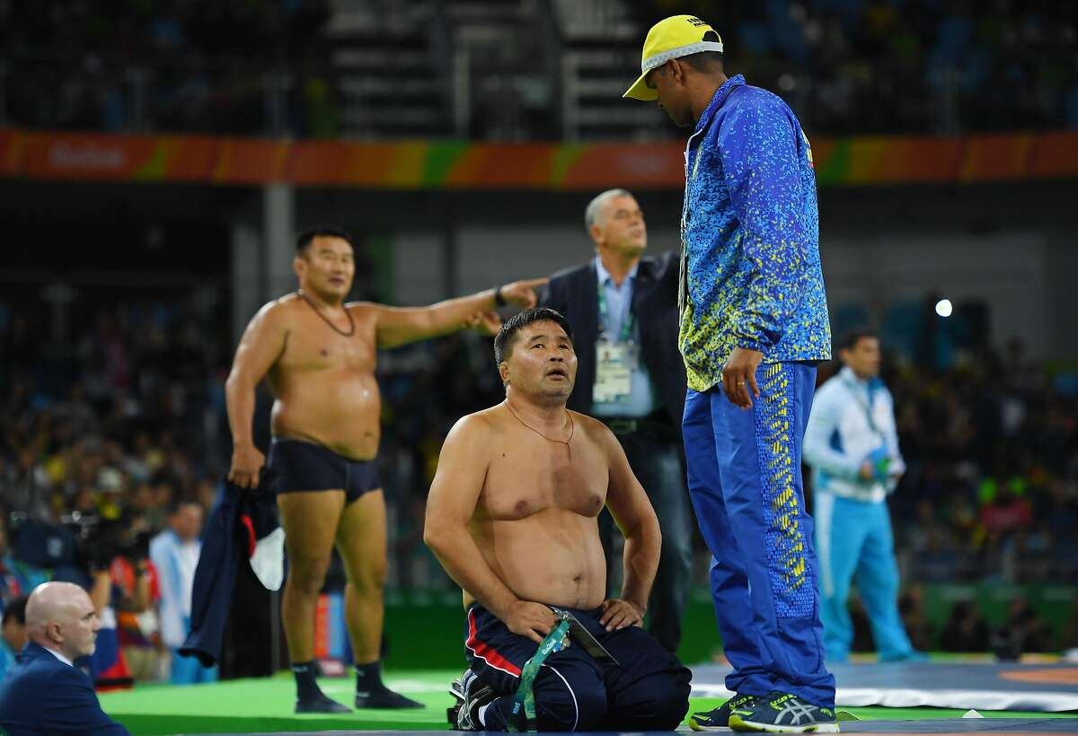 Mongolias coaches protest the judges decision after Mandakhnaran Ganzorig (red) of Mongolia is defeated by Ikhtiyor Navruzov (blue) of Uzbekistan in the Men's Freestyle 65kg Bronze match against on Day 16 of the Rio 2016 Olympic Games at Carioca Arena 2 on August 21, 2016 in Rio de Janeiro, Brazil. (Photo by Laurence Griffiths/Getty Images)