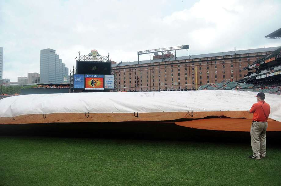 BALTIMORE, MD - AUGUST 21:  The grounds crew puts the tarp on the field before the game between the Baltimore Orioles and the Houston Astros at Oriole Park at Camden Yards on August 21, 2016 in Baltimore, Maryland. The start of the game was delayed due to inclement weather. Photo: Greg Fiume, Getty Images / 2016 Getty Images