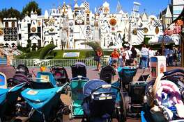 "PARK AND RIDE: Strollers are a familiar sight at Southern California theme parks such as Disneyland. Parents cite convenience and safety as the reasons for relying on the devices, but some pediatricians caution against keeping toddlers strapped in for too long. -- P069887.HE.0903.strollers1.GAW--Story is on theory that overuse of strollers may be one contributor to childhood obesity. At Disneyland's ""It's a Small World attraction a mix of rental strollers and strollers brought into the park by guests sit outside as guest enjoy the ride. Photo taken on Wed Sept 3, 2003."