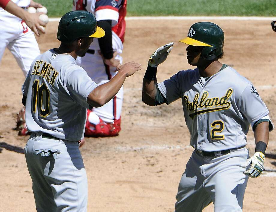 Khris Davis (2) is greeted by Marcus Semien after Davis' two-run homer in the fourth. Photo: David Banks, Getty Images
