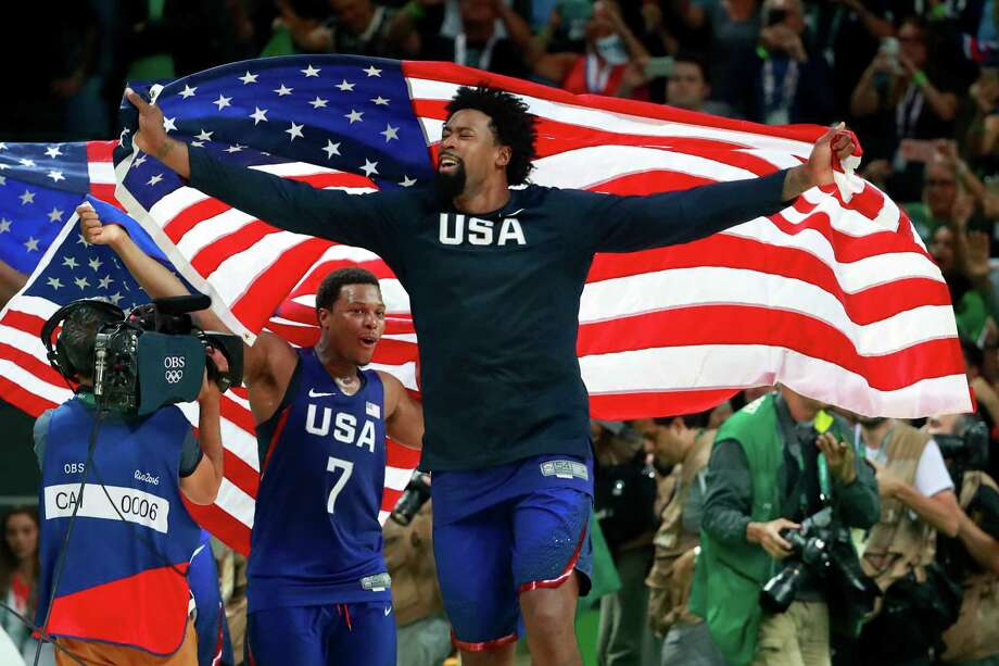 DeAndre Jordan, center, and Kyle Lowry of the U.S. celebrate with American flags after the men's basketball gold medal game against Serbia at Carioca Arena 1 during the 2016 Summer Games in Rio de Janeiro, Aug. 21, 2016. The U.S. team won 96-66 to take the gold medal. (Doug Mills/The New York Times) Photo: DOUG MILLS, NYT / NYTNS