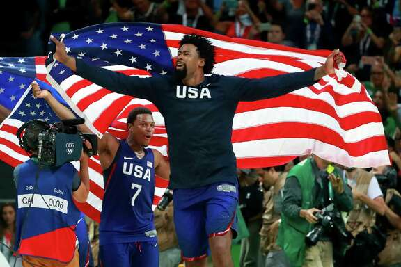 DeAndre Jordan, center, and Kyle Lowry of the U.S. celebrate with American flags after the men's basketball gold medal game against Serbia at Carioca Arena 1 during the 2016 Summer Games in Rio de Janeiro, Aug. 21, 2016. The U.S. team won 96-66 to take the gold medal. (Doug Mills/The New York Times)